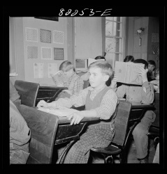 Boy at Desk Looking Forward Photograph
