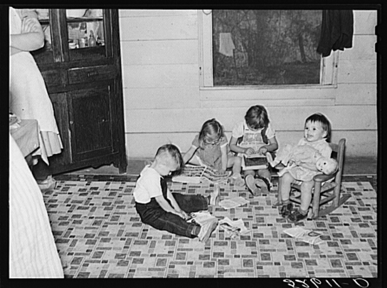 Children playing and cutting out pictures from Sears Roebuck catalogue