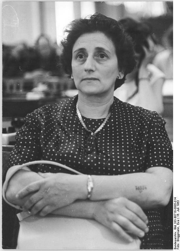 Zentralbild Brüggmann 16.7.1963 Letzter Tag der Beweisaufnahme im Globke-Prozeß. Vor dem 1. Strafsenat des Obersten Gerichts der DDR hat am 16.7.1963 der letzte Tag der Beweisaufnahme in der Hauptverhandlung gegen Globke begonnen. Neben einigen Zeugenaussagen wird das Gericht ein weiteres Gutachten entgegennehmen. UBz: Das holländische Ehepaar Eva und Jack Furth, beide durch mehrere Konzentrationslager geschleppt und gequält, machten sich namens der Zehntausende Verfolgten der Niederlande, zum Ankläger. Frau Furth (unser Bild) fügte den zahllosen Beispielen über Marterungen gesunder und blutjunger Frauen und Mädchen in Auschwitz, Dachau, Bergen-Belsen und Ravensbrück neue grausame Beispiele hinzu.
